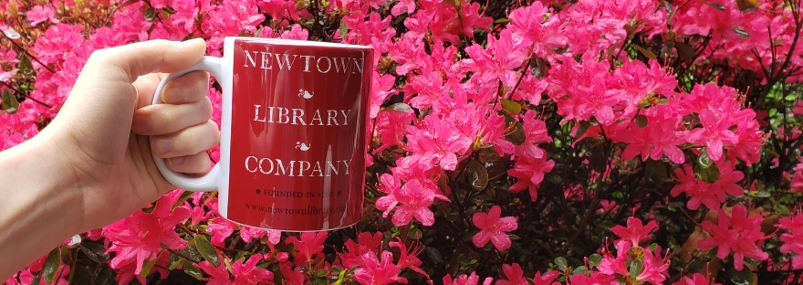 Hand holding Newtown Library Company mug in front of pink flowers